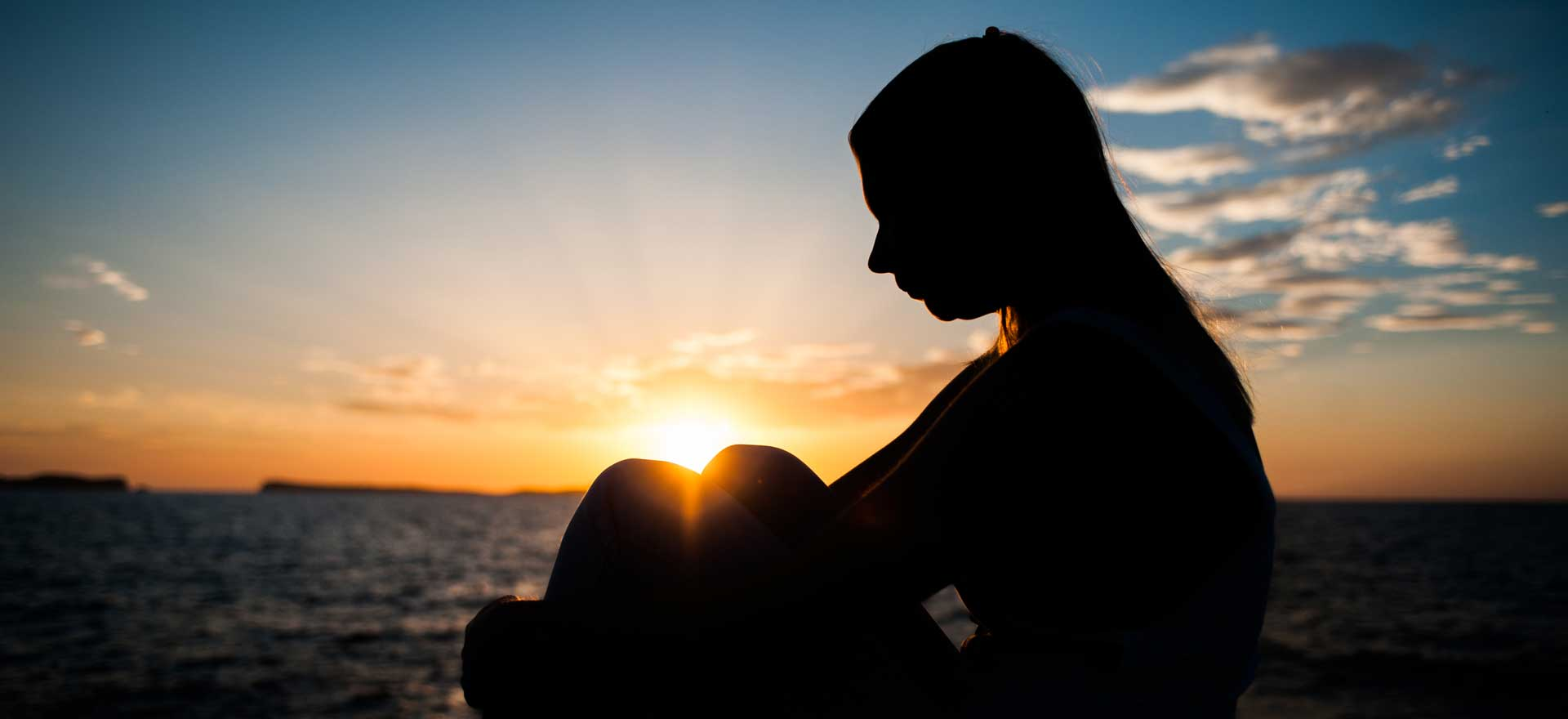 Girl Sitting by Sunset